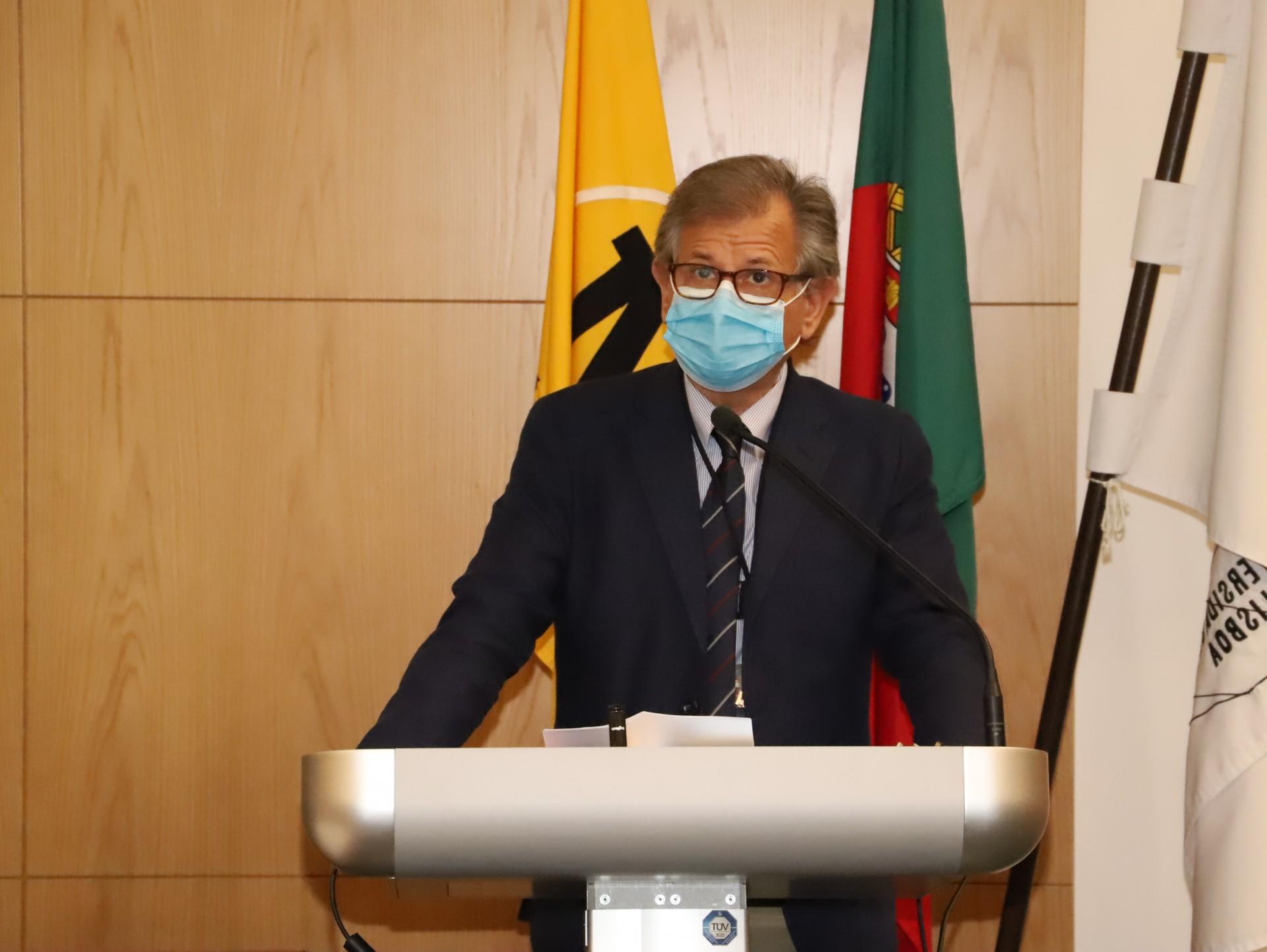 Homem de máscara e fato a discursar