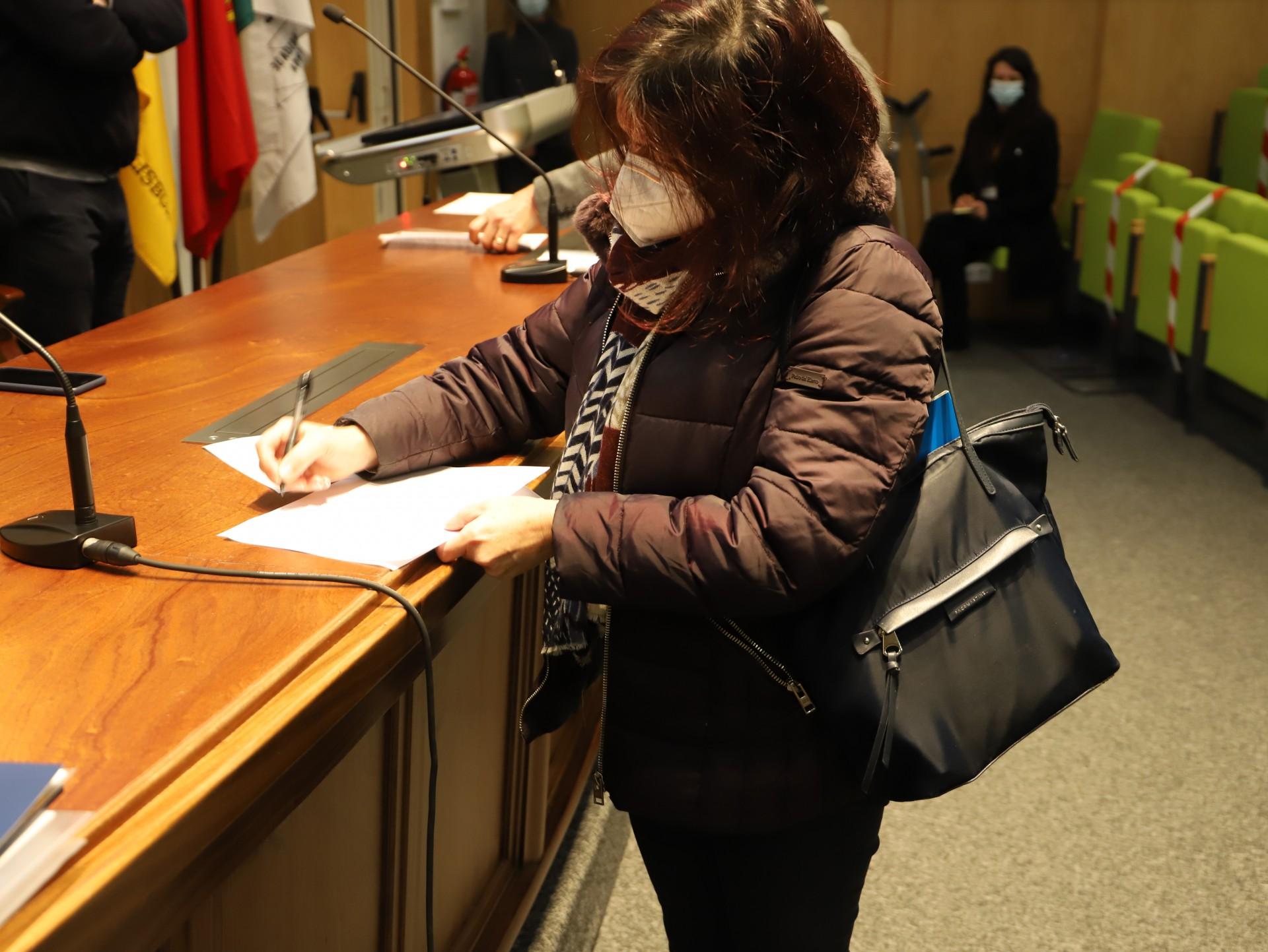 mulher assina documento