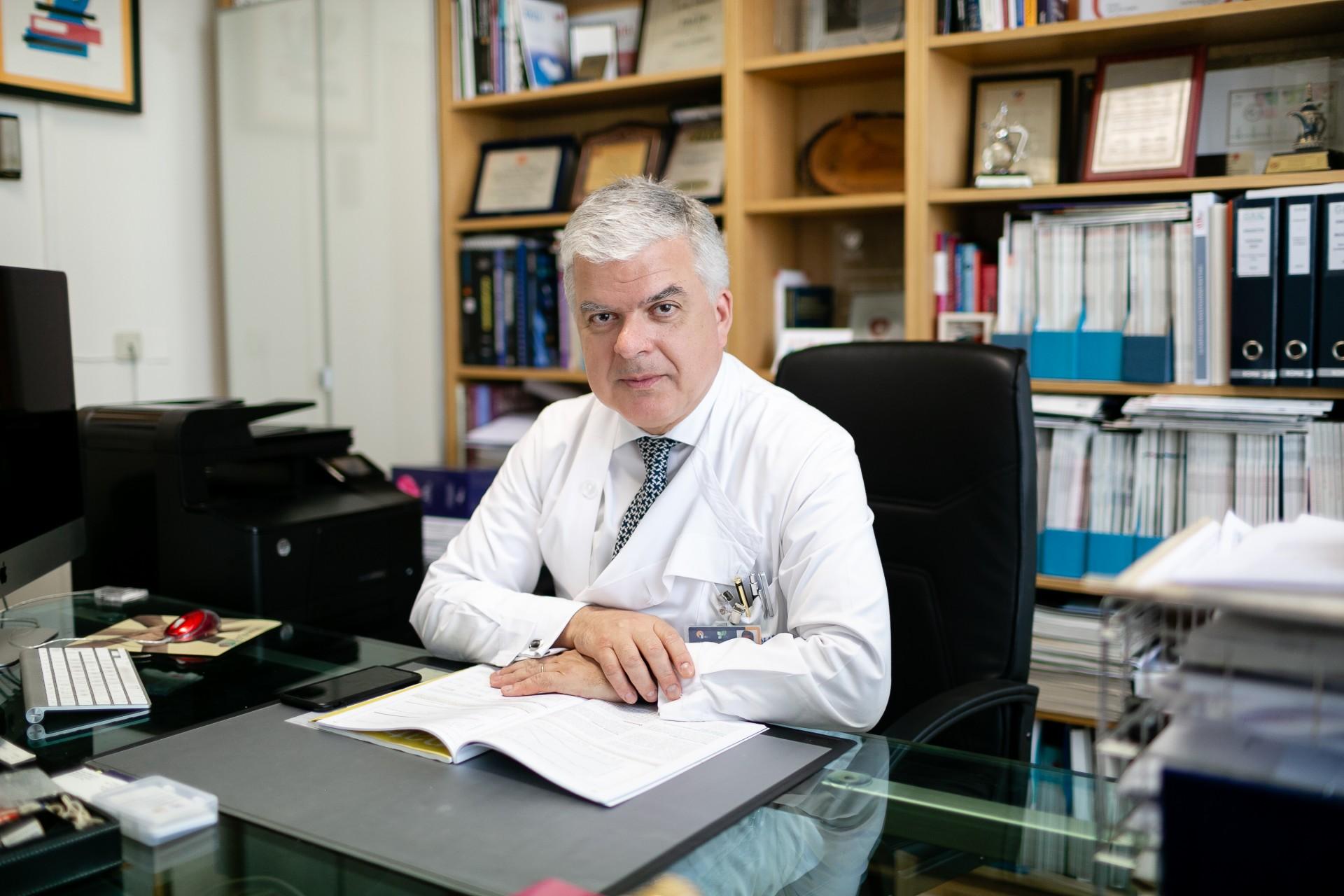 Homem sentado à secretária com braços assentes em livro