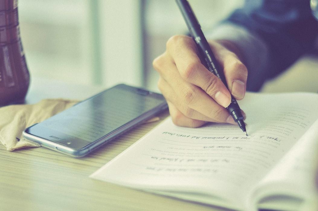 mão de um rapaz a escrever num caderno