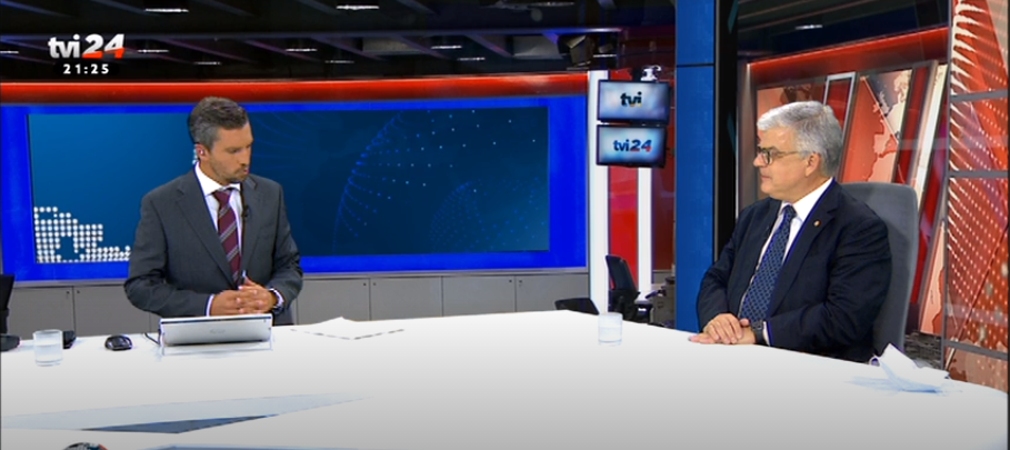 dois homens sentados em mesa de entrevista