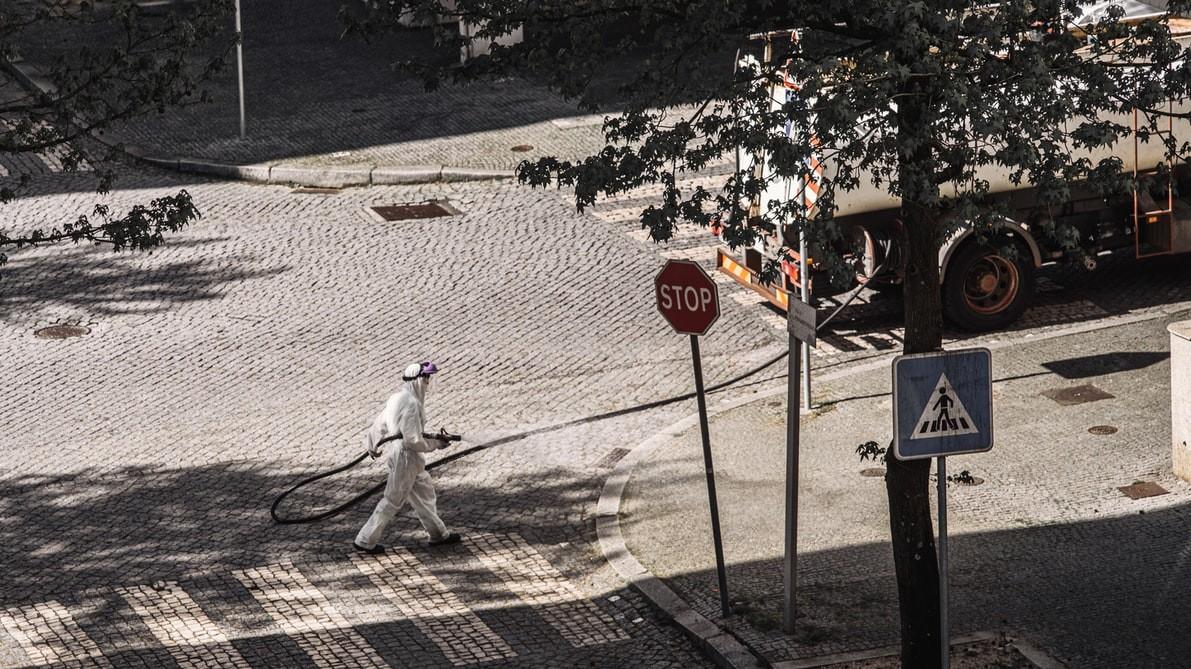 homem a desinfetar a rua